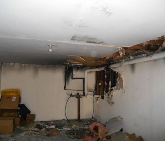 Room with fire damage and hole in a ceiling
