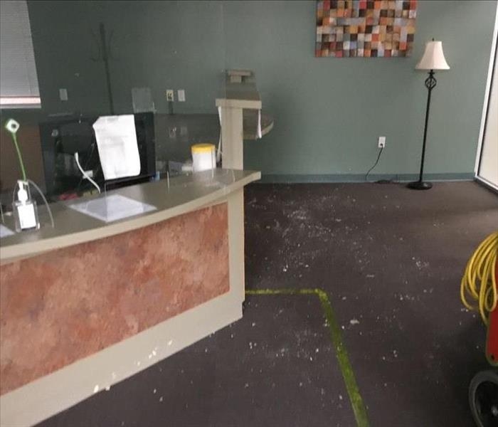 Front desk with debris on carpet and SERVPRO equipment