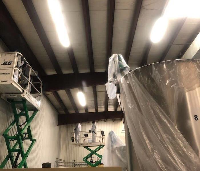 SERVPRO techs on cherry pickers cleaning walls in manufacturing plant