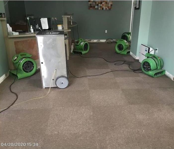 SERVPRO air movers in a room with a missing baseboard
