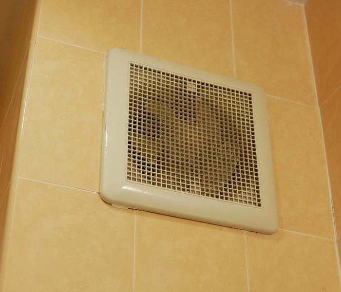 A fan in a bathroom that had dust on it.