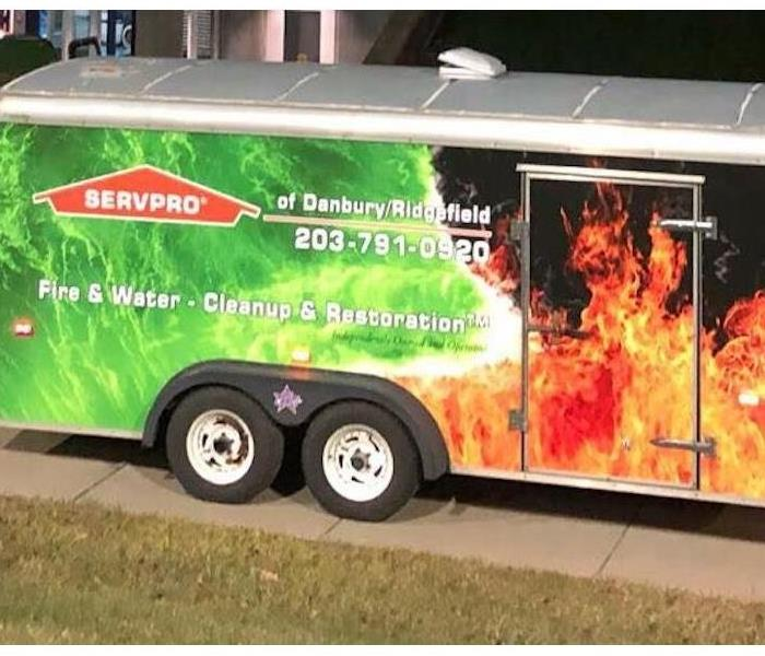 A SERVPRO enclosed trailer parked in a driveway.